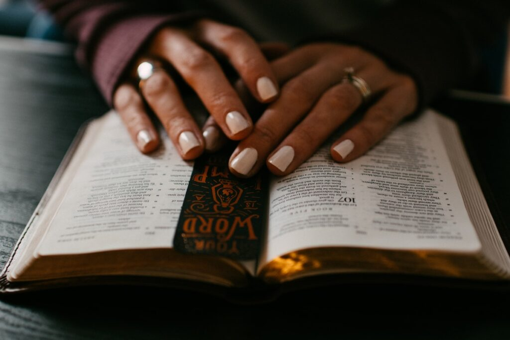 Black woman's hands with white nail polish, rest on an open bible with a bookmark inside.