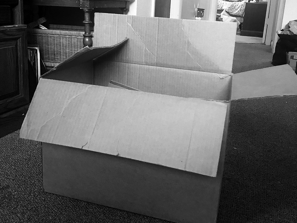 Black and white photo of a corrugated box, the box is a bit tattered and the flaps are open, but one is folding into the box, while the others are falling outward.